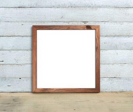 La maqueta de marco de madera antiguo cuadrado se encuentra en una mesa de madera sobre un fondo de madera pintado de blanco. Estilo rústico, belleza sencilla. Render 3D. Foto de archivo