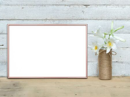 Rose Gold A4 horizontal Frame mockup near a bouquet of lilies stands on a wooden table on a painted white wooden background. Rustic style, simple beauty. 3 render.