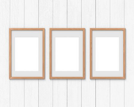 Set of 3 vertical wooden frames mockup with a border hanging on the wall. Empty base for picture or text. 3D rendering. Stock Photo
