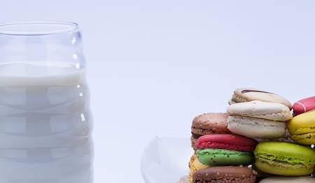 close up shot of various kind of fresh macaroons arrangement with a glass of milk