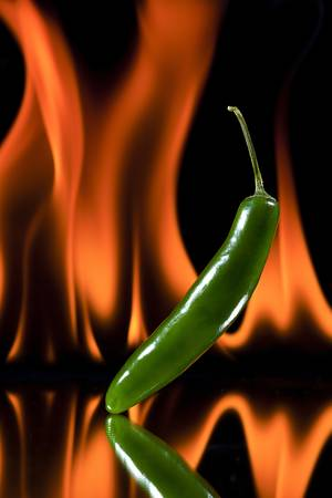 Fresh green jalapeno with real flame background