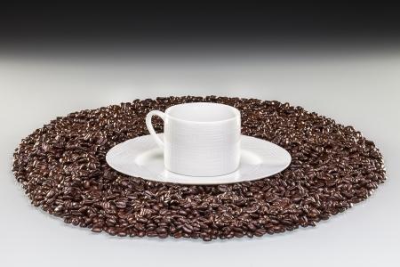 tasse de caf�, lit de graine de caf�,table blanche,fond noir