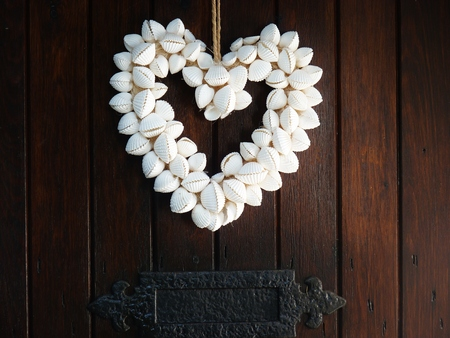 photo of object s: heart made from shells hanging on door