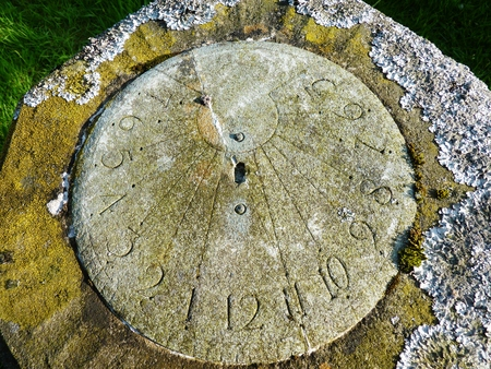 sundial covered with lichen old stone