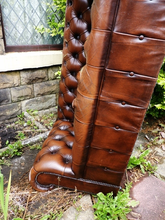 couch: brown leather couch left outdoors
