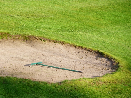 sand pit: rake at a golf course in sand pit