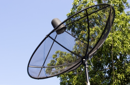 parabolic mirror: Satellite dish and cloudy blue sky background  and tree behind Stock Photo