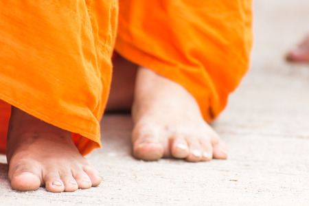 Monks walking on a street for receive food offerings on morning in Buddhist Sabbath