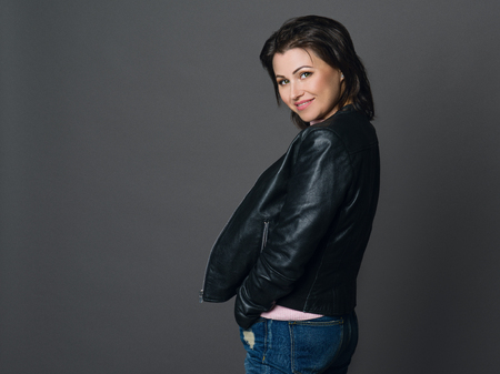 Portrait of beautiful woman with dark hair and green eyes. Dressed in a black leather jacket and jeans.