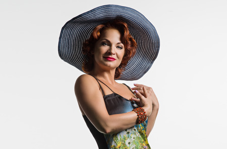 Portrait of a mature woman with red hair and a hat. Photo taken in studio on a white background.