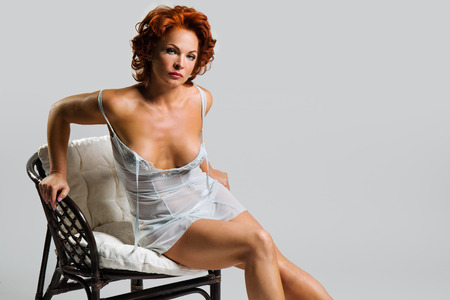 Sexy beautiful woman with red hair sitting on a chair