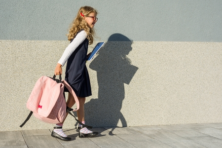 Schoolgirl with notebooks in hand. A girl with a backpack goes to school.  Back to school!