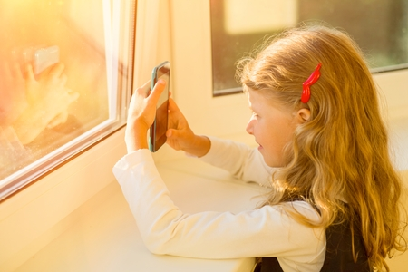 Covered image of a charming little girl with her blond hair, relaxing near the window,  using wi-fi on a mobile phone in a green case, enjoying an online connection after school hours