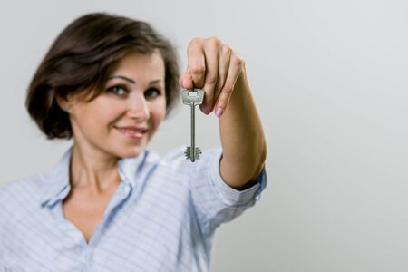 Adult smiling business woman or real estate agent showing keys from new home. Success in the concept of business. Stock Photo