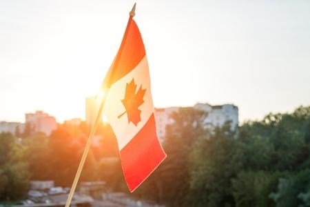 夕日を背景に窓からカナダの旗