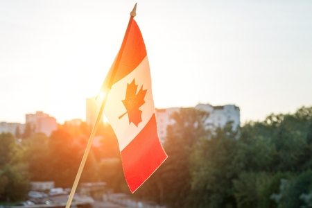 Flag of Canada from window on sunset background Stok Fotoğraf