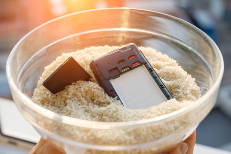 Dropped your phone in water - The fix is rice. Wet smartphone repair in rice Stock Photo