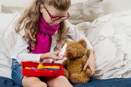 Sick child girl in glasses, heals his sick Teddy bear Stock Photo