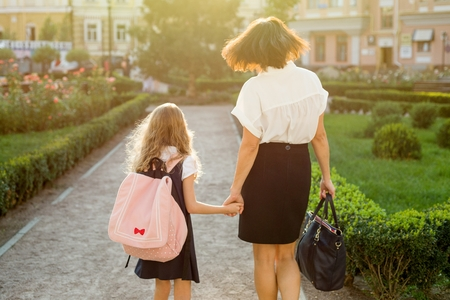Mother taking daughter to school. Back view.