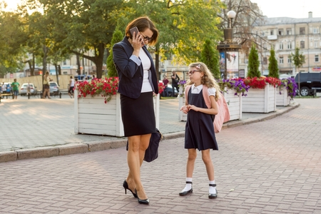 Mother businesswoman takes the child to school. Urban background
