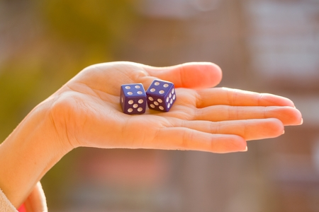 Dice 4 4 in the female hand, sunset background. Gambling devices. Game of chance concept.