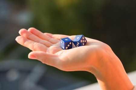 Dice 1 1 in the female hand, sunset background. Gambling devices. Game of chance concept. Stock Photo