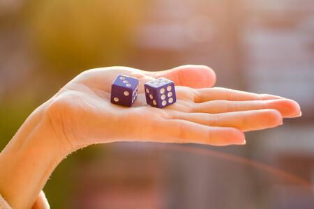 Dice 3 5 in the female hand, sunset background. Gambling devices. Game of chance concept. Stock Photo