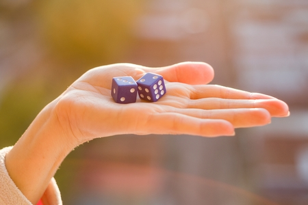Dice 2 3 in the female hand, sunset background. Gambling devices. Game of chance concept.