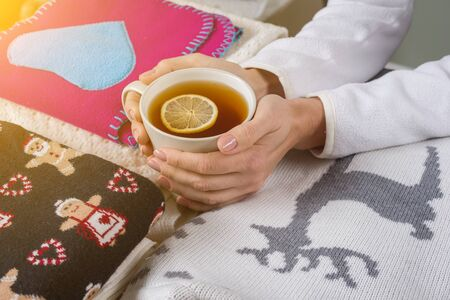 Christmas background winter clothes with traditional patterns, hot tea with lemon.