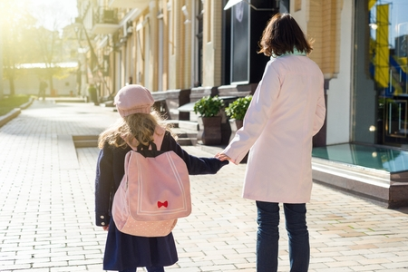 Mother taking child to school. Holding hands, background - autumn city. Woman and girl with backpack behind the back.