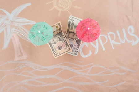 The concept of offshore banking and tax havens. A picture with dollar bills on a tropical beach, under a palm tree and an umbrella, on the beach the word CYPRUS