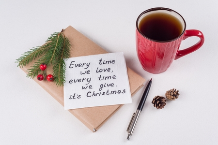 Merry Christmas greetings or wishes - Handwritten text with wishes on a napkin - Every time we love, every time we give, its Christmas Stock Photo