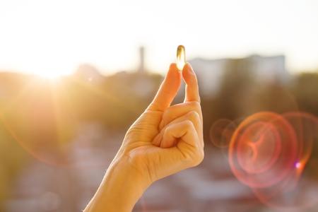 Hand einer Frau, die Fischöl Omega-3-Kapseln, städtischen Sonnenunterganghintergrund hält. Gesunde Ernährung, Medizin, Gesundheitswesen, Nahrungsergänzungsmittel und Leutekonzept
