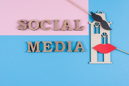 Text social media abstract wooden letters. Blue background with the image of house and pair of friends.