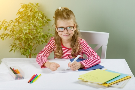 A junior schoolgirl with glasses writes something with her left hand in the notebook and sits at the table. Back to school concept. The child is left-handed.