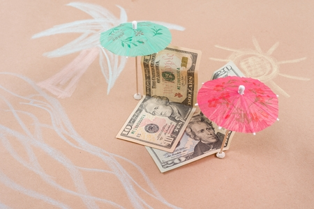 The concept of offshore banking and tax havens. Picture with dollar bills on a tropical beach, under a palm tree and an umbrella Stock Photo