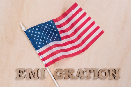Flag of the United States, word emigration in abstract letters. Wooden background Banco de Imagens