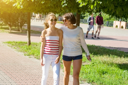 Mom and daughter talking, smiling, walking through the city park, on a summer day