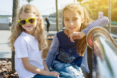 Two pretty little girls are looking at the camera and smiling. Background urban, summer, embankment of the river