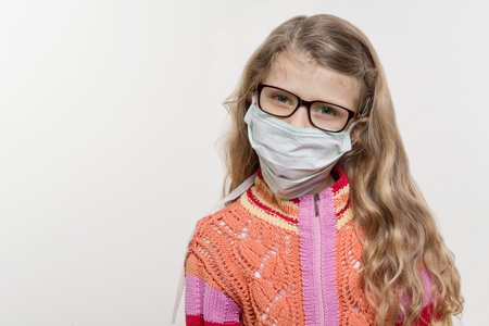 Girl child in medical mask. On a white background, copy space. Stock Photo