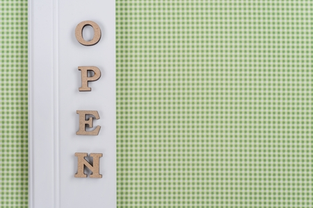 Word open, abstract wooden letters, green white background