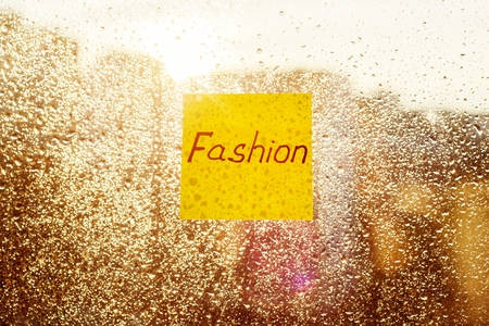 Sticker with text FASHION. Background sunny window with shiny rain drops, view of the modern city Stock Photo