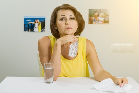 Woman  holding pills in her hand, taking pills.