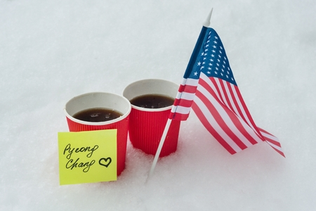 Kyiv UA, 21-12-2017, 2018 Winter Olympic Games with kinds of sport in PyeongChang, Republic of Korea, The flag of the USA team, two cups of fans with coffee and a sticker - PyeongChang with love.