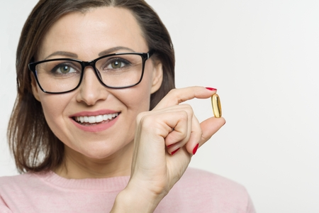 A woman holds a capsule with vitamin E, fish oil. white background, focus on the capsule