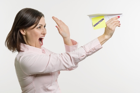 Middle-aged woman lets out a abstract paper airplane with the written word Addiction. White background.