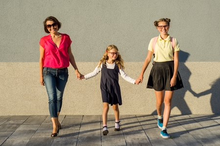 A happy loving family - mother and daughter of a schoolgirl, holding hands. Back to school