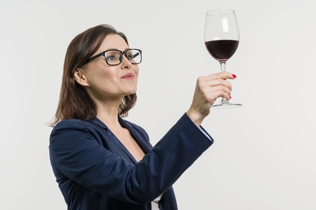 Business woman is holding and looking at a glass of red wine. White studio background.
