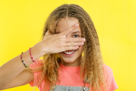 Smiling teenage girl embracing her eyes with fingers, she happily smiles into the camera on a yellow background.