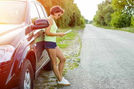 Cute female driver is traveling. Standing beside his car on a country road and watching a road map.